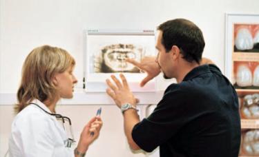 stomatolodzy przegladają zdjęcia uzebienia pacjenta